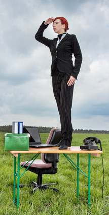 Business woman standing on the desk and looks out