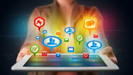 Girl presenting a tablet with colorful social icons and signs